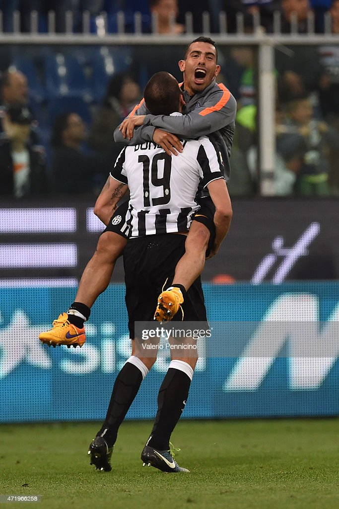 Leonardo Bonucci and Carlos Tevez of Juventus FC celebrate after beating UC Sampdoria 1-0 to win the Serie A Championships at the end of the Serie A match between UC Sampdoria and Juventus FC at Stadio Luigi Ferraris on May 2, 2015 in Genoa, Italy.
