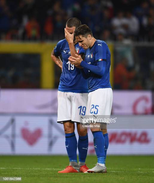 Leonardo Bonucci and Federico Chiesa of Italy stop to play and applaud at the 43rd minute of the game in homage to the 43 victims of the August 14...