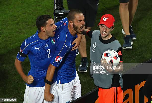 Leonardo Bonucci of Italy celebrates scoring his team's first goal with his team mateMattia De Sciglio and a ball boy during the UEFA EURO 2016...