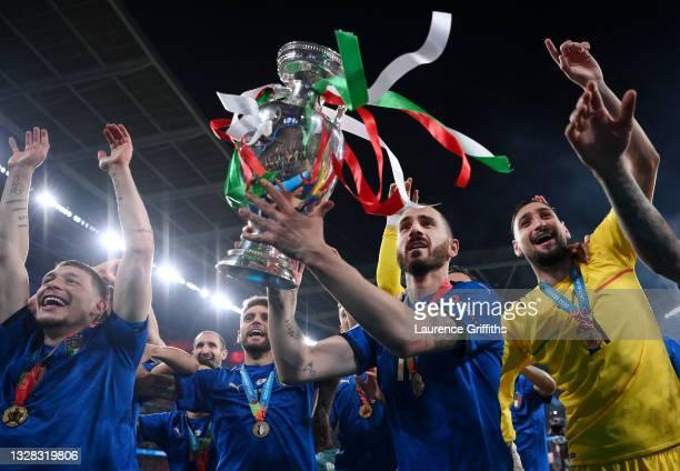 Leonardo Bonucci of Italy celebrates with the European Championship Trophy alongside Andrea Belotti and Gianluigi Donnarumma during the UEFA Euro...