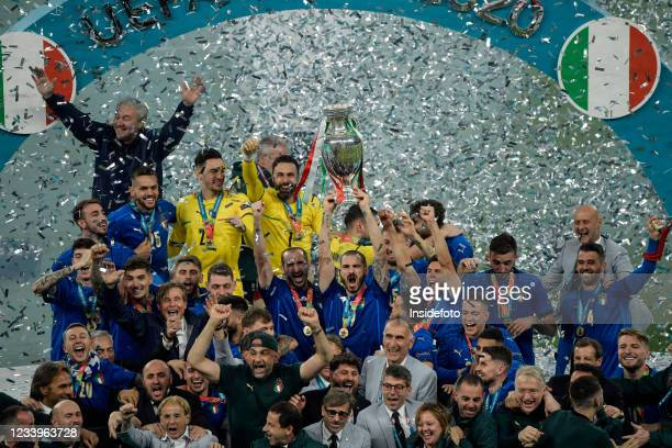 Leonardo Bonucci of Italy holds the trophy while the italian team celebrate the victory during the prize ceremony at the end of the Uefa Euro 2020...