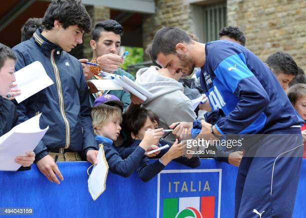 Leonardo Bonucci of Italy sign autographs for fan after a training session at Coverciano on May 27 2014 in Florence Italy