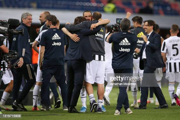 Leonardo Bonucci of Juventus embraces team mate Giorgio Chiellini and Head coach Andrea Pirlo as players and staff celebrate following the results...