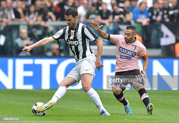 Leonardo Bonucci of Juventus holds off the challenge from Fabrizio Miccoli of Palermo during the Serie A match between Juventus and US Citta di...