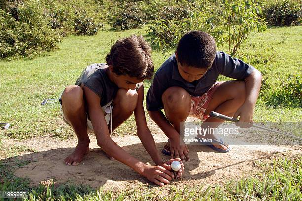 Leonardo Gomes Marques teaches his cousin Loami Marques how to use grass sticks to improvise for a golf tee May 14 2003 at Japeri Municipal Public...