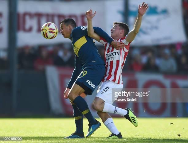 Leonardo Jara of Boca Juniors fights for the ball with Matias Pellegrini of Estudiantes during a match between Estudiantes and Boca Juniors as part...