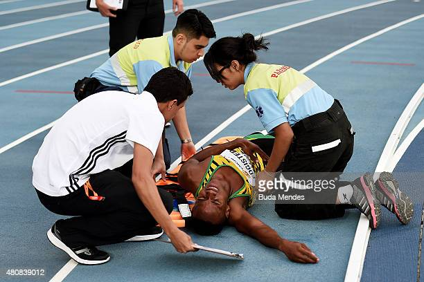 Leonardo Ledgister of Jamaica receives medical attention after an injury during round one of the Boys 400 Meters Hurdles on day one of the IAAF World...