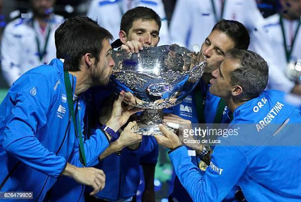 Leonardo Mayer, Guido Pella, Federico Del Bonis, Juan Martin Del Potro of Argentina and Argentina team captain Daniel Orsanic kiss the trophy after...