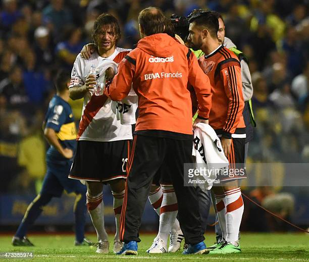 Leonardo Ponzio of River Plate tries to wash off tear gas during a second leg match between Boca Juniors and River Plate as part of round of sixteen...