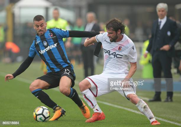 Leonardo Spinazzola of Atalanta BC competes for the ball with Andrea Poli of Bologna FC during the Serie A match between Atalanta BC and Bologna FC...