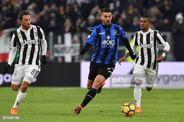 Leonardo Spinazzola of Atalanta BC in action against Claudio Marchisio and Douglas Costa of Juventus during the TIM Cup match between Juventus and...
