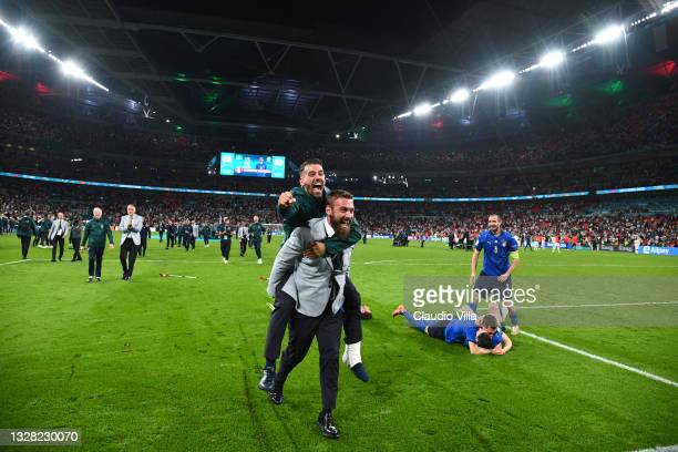 Leonardo Spinazzola of Italy jumps on the back of Daniele De Rossi, Assistant Coach of Italy as they celebrate their side's victory after the UEFA...