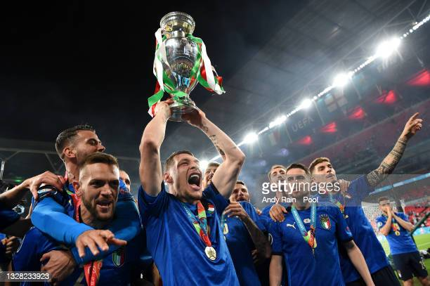 Leonardo Spinazzola, Rafael Toloi, Andrea Belotti and Jorginho of Italy celebrate with The Henri Delaunay Trophy following their team's victory in...