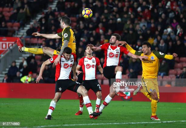 Leonardo Ulloa of Brighton and Hove Albion and Jack Stephens of Southampton battle to win a header during the Premier League match between...