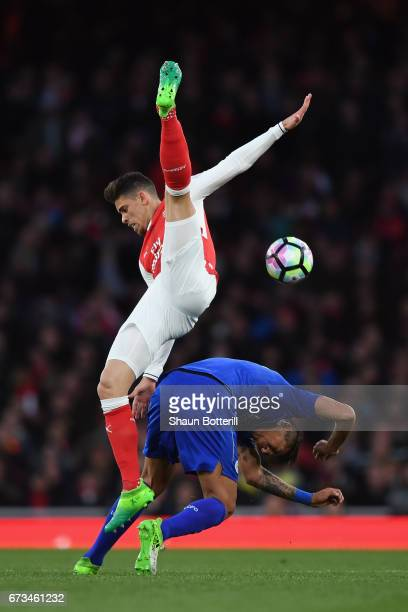Leonardo Ulloa of Leicester City and Gabriel of Arsenal clash during the Premier League match between Arsenal and Leicester City at the Emirates...