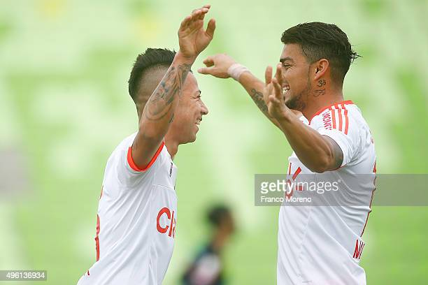 Leonardo Valencia of U de Chile celebrates with Paulo Magalhaes after scoring the opening goal during a match between Deportes Iquique and U de Chile...