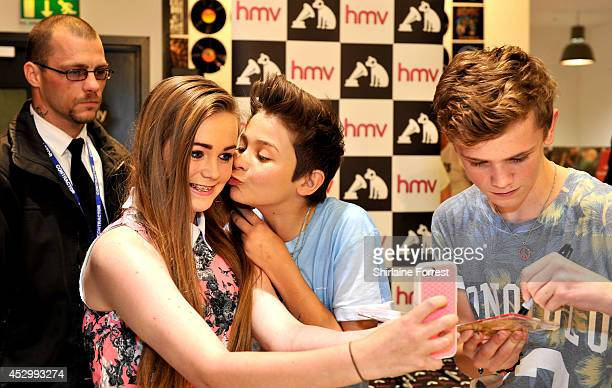 Leondre Devries of Bars and Melody Britain's Got Talent finalists kisses a fan on the cheek for a selfie while signing copies of their debut single...