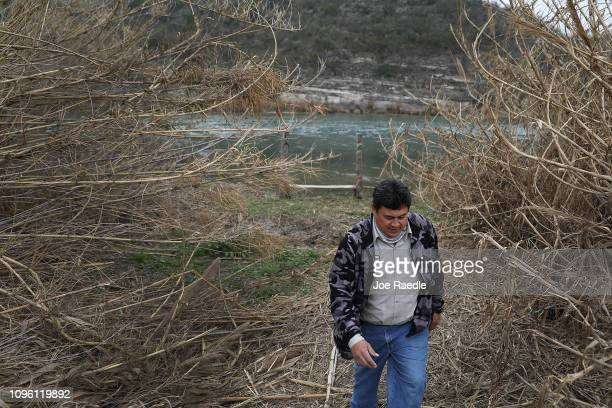 Leonel Calderon stands next to the Rio Grande river which marks the boundary between the United States and Mexico as it flows past the back yard of...