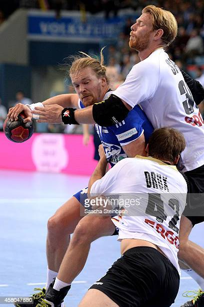 Leonel Henrik Ojala of Finland is tackled by Paul Drux and Manuel Spaeth of Germany during the 2016 European Men's Handball Championship qualifier...