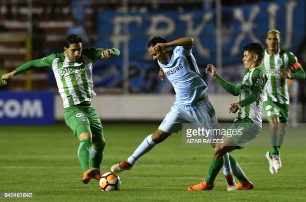 Leonel Justiniano of Bolivia's Bolivar vies for the ball with Jorman Campuzano and Gonzalo Castellani of Atletico Nacional of Colombia during their...