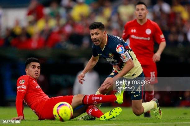 Leonel Lopez of Toluca fights for the ball with Oribe Peralta of America during the 12th round match between America and Toluca as part of the Torneo...