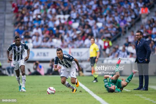 Leonel Vangioni of Monterrey drives the ball as Brayan Garnica of Atlas falls to the ground during the 9th round match between Monterrey and Atlas as...