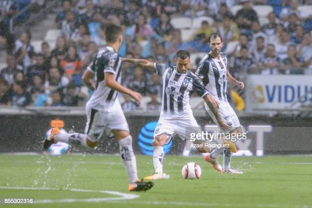 Leonel Vangioni of Monterrey kicks the ball while observed by teammates Jonathan Gonzalez and Jose Maria Basanta during the 11th round match between...