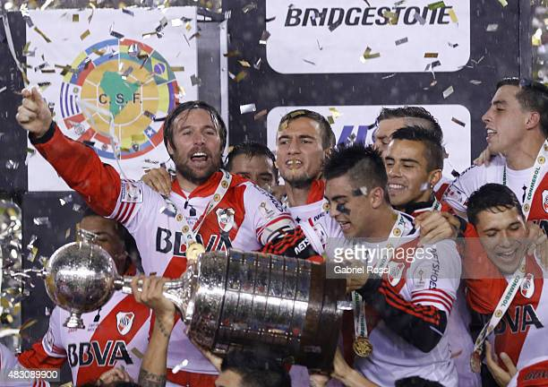Leonel Vangioni of River Plate lifts the trophy to celebrate with his teammates after winning a final match between River Plate and Tigres UANL as...