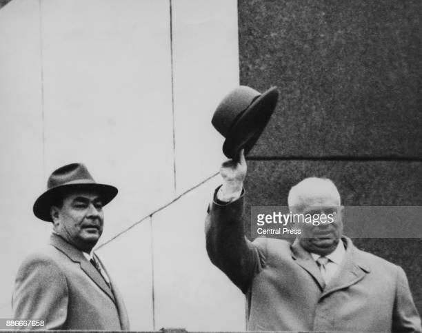 Leonid Brezhnev and Nikita Khrushchev wave from Lenin's Tomb in Moscow after the announcement that Khrushchev was resigning as First Secretary of the...