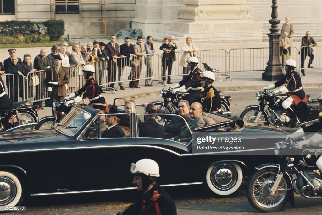 Leonid Brezhnev (1906-1982), General Secretary of the Communist Party of the Soviet Union, pictured on left with President of France, Georges Pompidou (1911-1974) sitting together in the rear of an open top limousine as they are escorted by motorcycle outriders past residents through the streets of Paris at the start of a visit by the Soviet Premier to France on 25th October 1971.