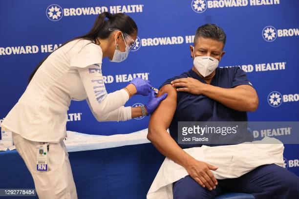 Leonida Lipshy, RN in the COVID unit at the Broward Health Medical Center, gives Jaime Carrillo, M.D. Internal Medicine, Broward Health Imperial...