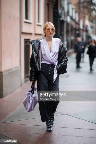 Leonie Hanne is seen wearing black puffer jacket pink blouse cropped wide leg pants pink bag heels outside Nanushka during New York Fashion Week...