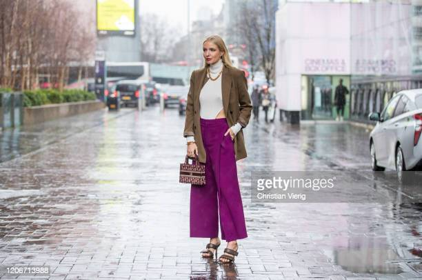 Leonie Hanne is seen wearing body, purple wide leg pants, Dior bag, blazer, brown sandals outside Roland Mouret during London Fashion Week February...