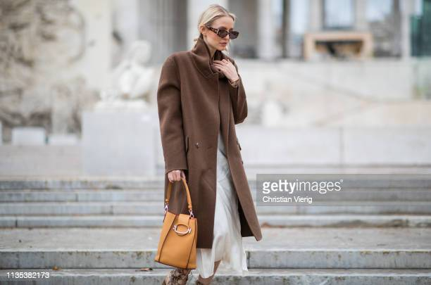 Leonie Hanne is seen wearing brown coat orange bag dress outside Tods lunch during Paris Fashion Week Womenswear Fall/Winter 2019/2020 on March 05...