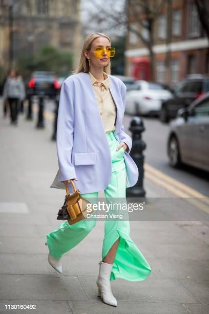 Leonie Hanne is seen wearing green flared pants with slit purple blazer Boyy bag yellow button shirt outside AWAKE Awake during London Fashion Week...