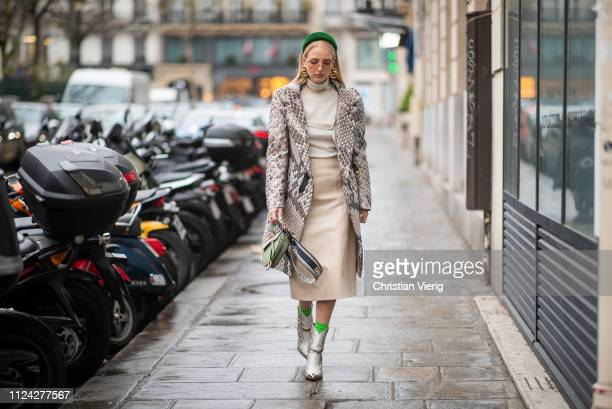 Leonie Hanne is seen wearing green Prada head band Dior necklace earings Dior bag boots with snake print beige skirt turtleneck coat with snake print...