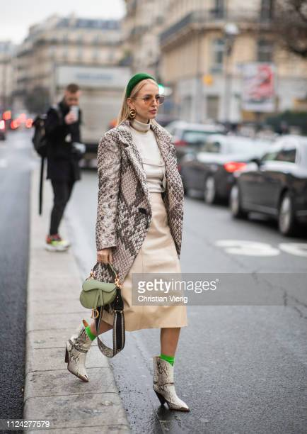 Leonie Hanne is seen wearing green Prada head band, Dior necklace, earings, Dior bag, boots with snake print, beige skirt, turtleneck, coat with...