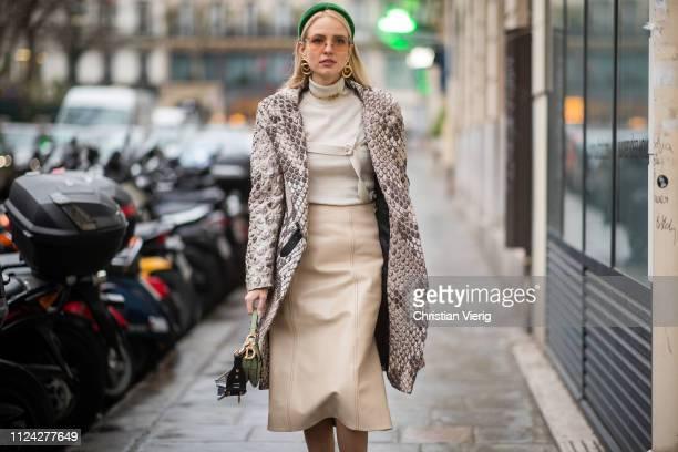 Leonie Hanne is seen wearing green Prada head band, Dior necklace, earings, Dior bag, beige skirt, turtleneck, coat with snake print outside Jean...