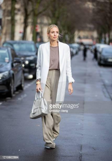 Leonie Hanne is seen wearing grey wide leg pants, white coat, bag outside Akris during Paris Fashion Week - Womenswear Fall/Winter 2020/2021 : Day...