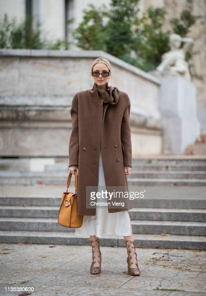 Leonie Hanne is seen wearing laced boots with snake print brown coat orange bag dress outside Tods lunch during Paris Fashion Week Womenswear...