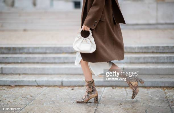 Leonie Hanne is seen wearing laced boots with snake print, brown coat, bag, dress outside Tods lunch during Paris Fashion Week Womenswear Fall/Winter...
