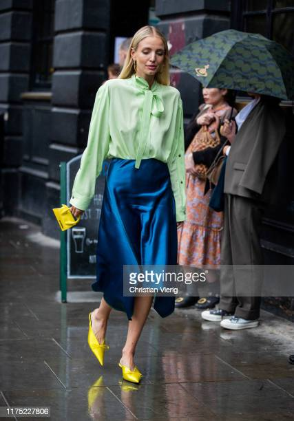 Leonie Hanne is seen wearing navy silk skirt green blouse with tie yellwo mini bag Jacquemus outside Christopher Kane during London Fashion Week...