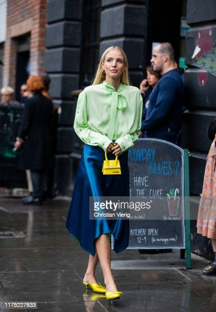 Leonie Hanne is seen wearing navy silk skirt, green blouse with tie, yellwo mini bag Jacquemus outside Christopher Kane during London Fashion Week...