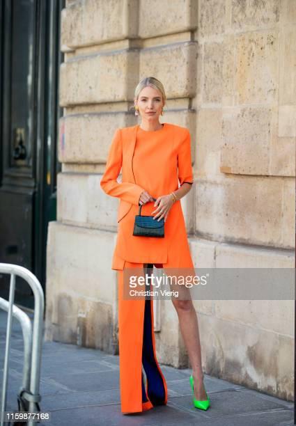 Leonie Hanne is seen wearing orange dress, green mini bag, neon Balenciaga heels outside RVDK Ronald Van Der Kemp during Paris Fashion Week - Haute...