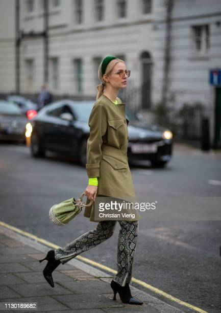 Leonie Hanne is seen wearing pants with snake print olive jacket hair hoop outside Toga during London Fashion Week February 2019 on February 16 2019...