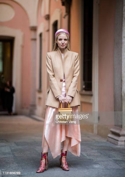 Leonie Hanne is seen wearing pink hair loop, beige blazer, asymmetric skirt, yellow Boyy bag on Day 2 Milan Fashion Week Autumn/Winter 2019/20 on...