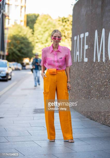 Leonie Hanne is seen wearing pink sheer Miu Miu button shirt, orange bag, Jacquemus mini bag worn as a fanny bag, pink sunglasses outside Ports 1961...