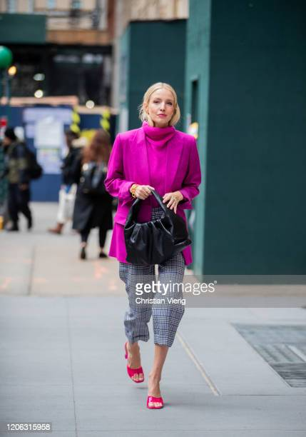 Leonie Hanne is seen wearing purple turtleneck and blazer black Bottega bag cropped grey checkered pants outside Michael Kors during New York Fashion...