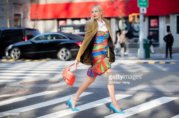 Leonie Hanne is seen wearing red Fendi bag, beige blazer, multi colored dress, white blouse outside Tory Burch during New York Fashion Week Fall /...
