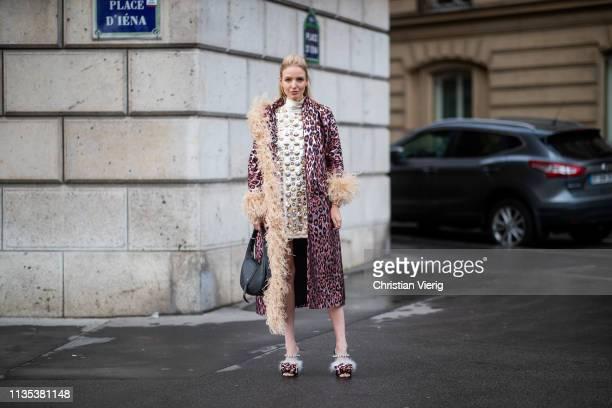 Leonie Hanne is seen wearing sleeveless dress coat bag heels outside Miu Miu during Paris Fashion Week Womenswear Fall/Winter 2019/2020 on March 05...